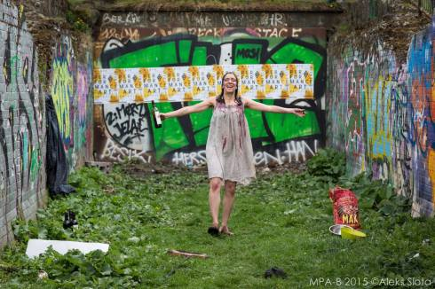 Sara Zaltash performing in Tuul: Sweetmud, which was in the 2013 Peep/Anatomy programme. Sara is in a graffiti-covered back yard. She is dressed in sackcloth and is holding a bottle of wine, which she has poured on herself. She looks celebratory. Photo by Aleks Slota.