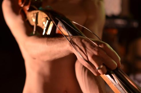 a naked man carresses a dying double bass