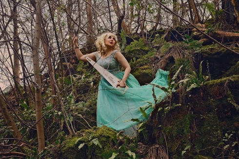 A person in a fabulous tuquoise dress is posing with a musical saw i the middle of spindly green woods