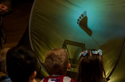 Three young children are gazing at a green tent, which has a shadow of a footprint on it.