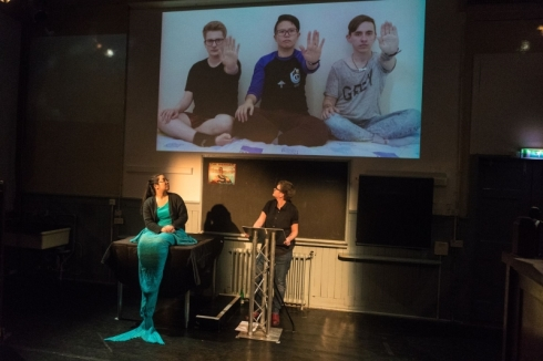 A still from the performance of Equivalence. In front, a Mermaid (blue-green tail, black sweater) and a speaker (black shirt, blue jeans) are looking up to a large screen. On the screen, three people are sat on a bed with their hands forward in the signal for